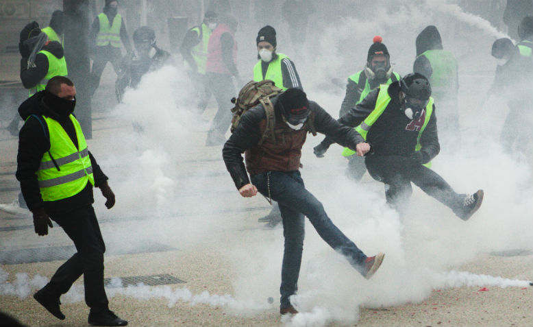 Yellow Vests kick away tear gas canisters. Photo: wikimedia commons