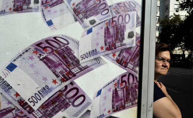 A woman stands a a bus station advertisinfg a lottery in Athens. Photo: AFP/Louisa Gouliamaki
