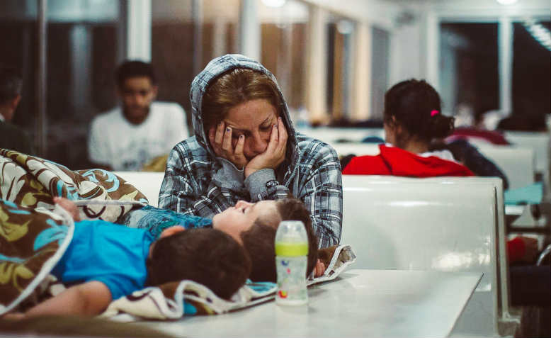 A refugee sleeps with her children on a ferry from Lesvos to Piraeus.