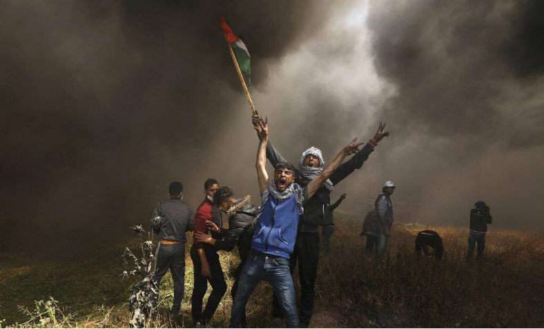 Palestinian protesters with flag stand with flag and arms up-stretched in anger or defiance, with a cloud of black smoke behind them