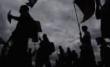 silhouette of strikers against a grey sky