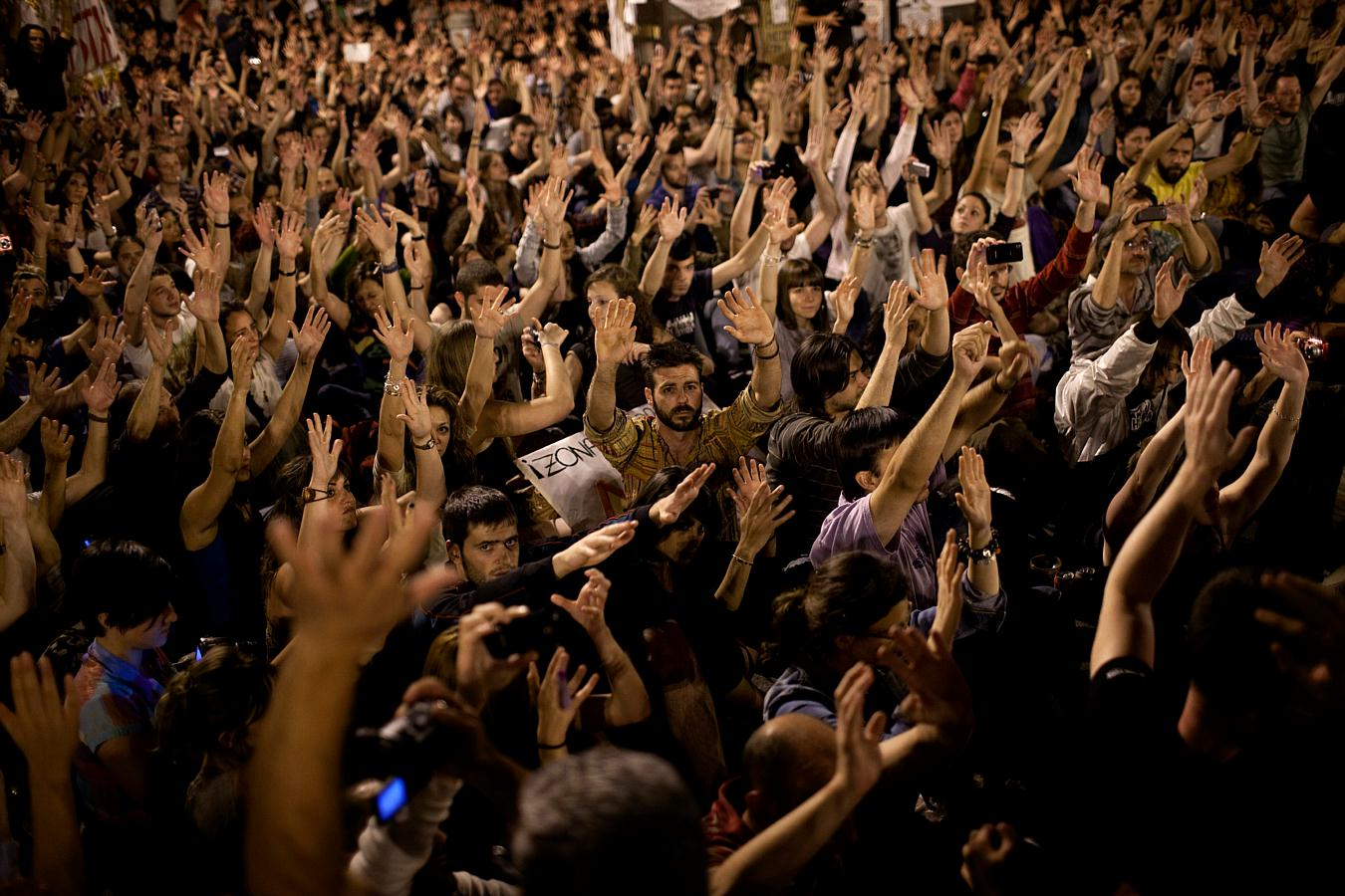 Demonstrators raise their hands during a protest at Sol square in Madrid, Monday, May 23, 2011. Photo: Emilio Morenatti