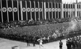 A runner carrying the Olympic torch into the Reich Sports Field to light the Olympic flame during the opening ceremonies of the 1936 Berlin Olympics.