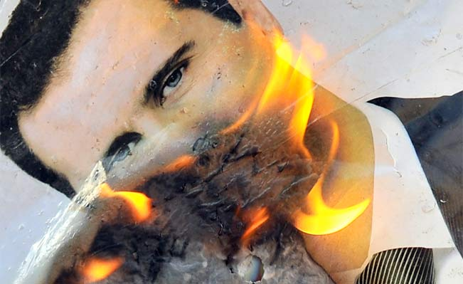 A portrait of the Syrian president, Bashar al-Assad, burning during clashes between rebels and Syrian troops near Aleppo. Photo: Bulent Kilic/AFP/Getty