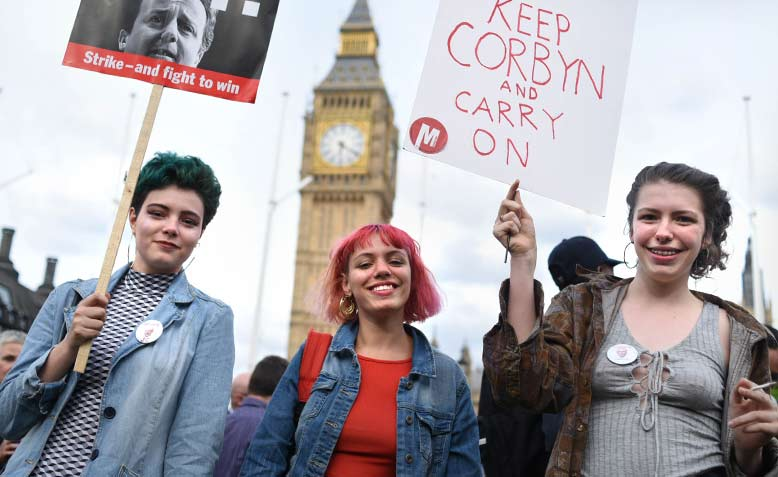 Three young women with placards in front of Big Ben, Defend Corbyn Rally, Parliament Square, London, 27 June 2016.  Photo: Jim Aindow/Flickr