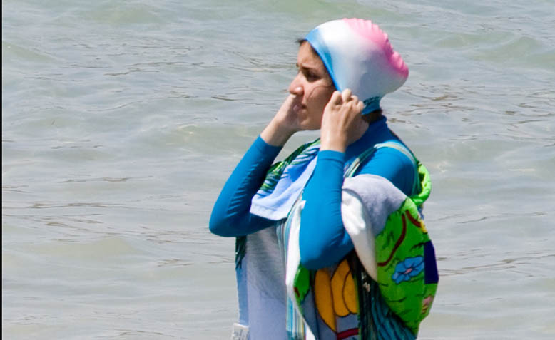 A woman wears a burkini on the beach. Photo: Wikipedia