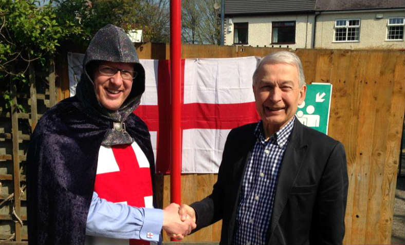 Frank Field MP stands smiling and shaking hands with a man dressed as St George - celebrating St George's day at a school in his Birkenhead constituency in 2015.