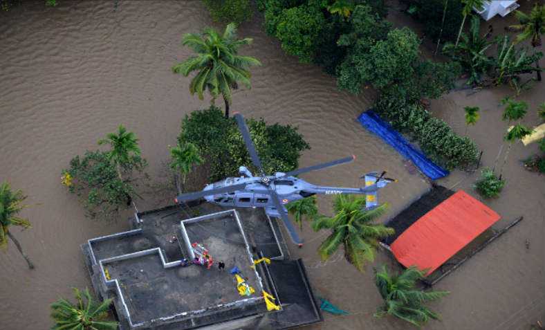 Indian Southern Naval Command helicopter hovers over a building amidst the flood in Kerala - people are being rescued below.