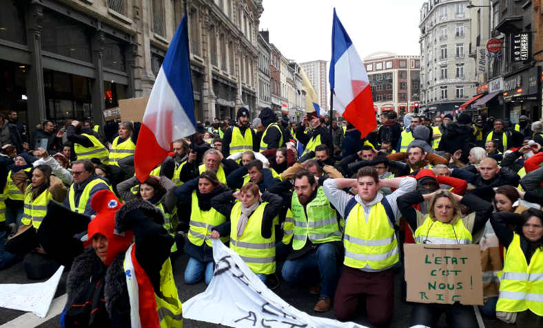 Gilets Jaunes in Lille on Saturday 8 December in mass solidarity gesture with the detained high school students of Mantes-la-Jolie, of whom around a hundred were put in the stress position illustrated when detained by armed police following their protest. Photo: @GiletsJaunes_FR