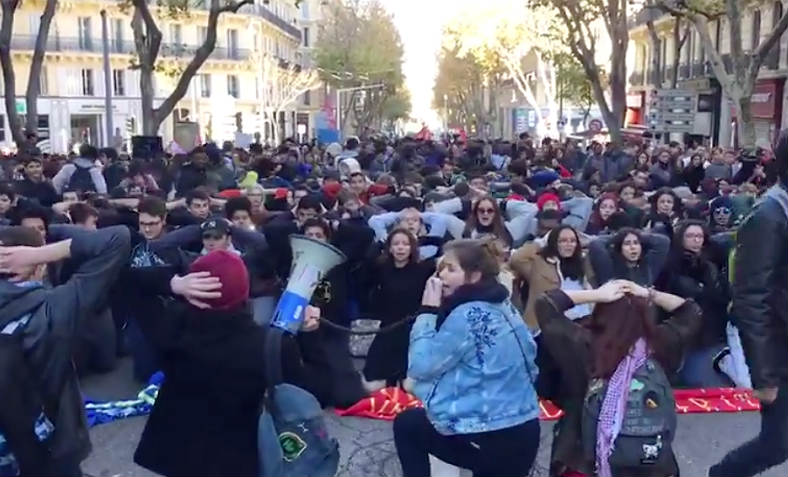 High school students marching in Marseille stop in the city centre to take up the mass knelt stress position in tribute/solidarity to the students of the Mates-la-Jolie Lycee whom were detained by police for hours in this manner.  It has become a symbolic gesture of defiance to Macron and violent state repression for the student movement and others. Photo: Video still, Twitter/laprovence
