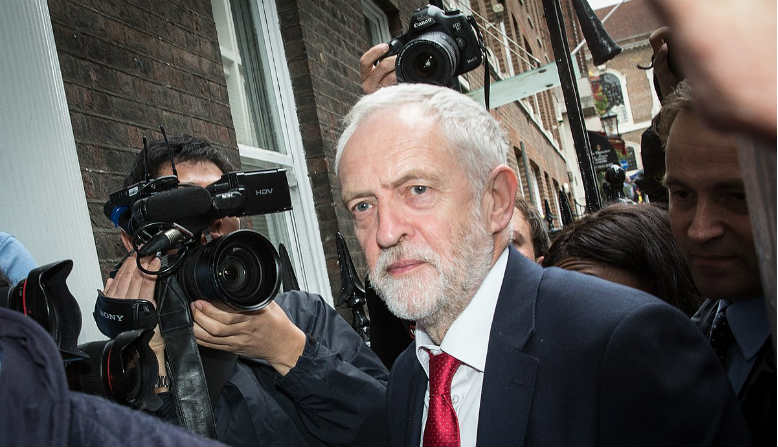 Jeremy Corbyn surrounded by photographers. (Source: Wiki Commons)