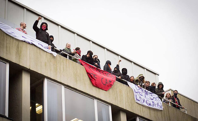 Occupiers, pictured, on the balcony of Bramber House and flying banners while chanting: 'Don't deport Luqman'.