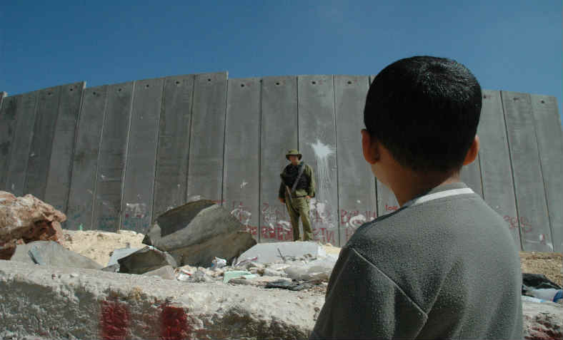 boy in front of soldier and separation wall
