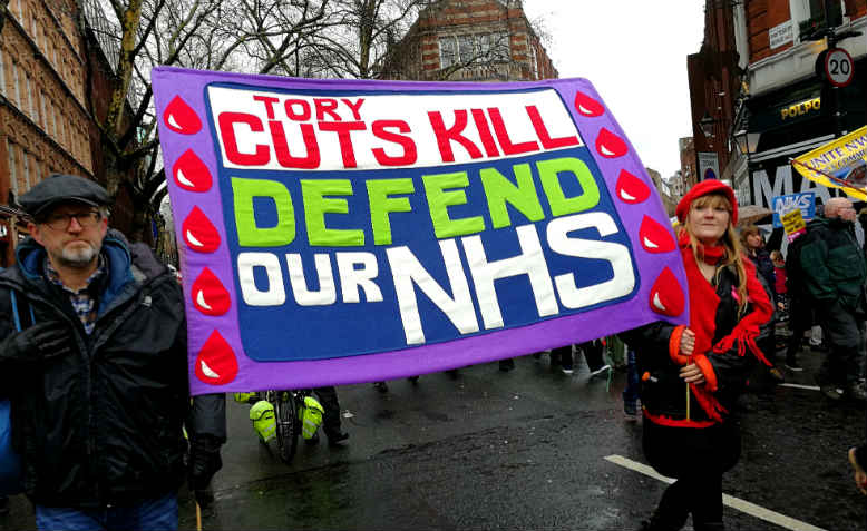 A brightly coloured banner on the Fund Our NHS march on Saturday 3rd February, reading 'Tory cuts kill ; Defend our NHS'