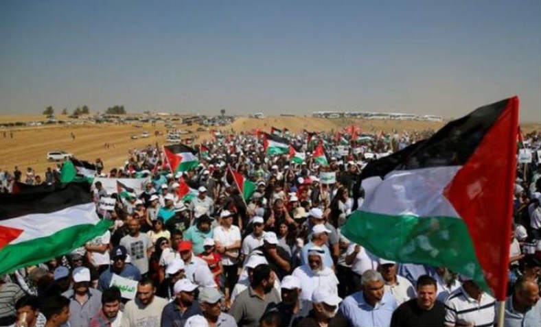 Tens of thousands of people on The Great Return March, holding Palestinian flags, make their way along the Israeli border at a distance of half a mile