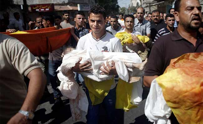 A Palestinian relative of the eight members of a family killed in an airstrike cries as he carries the body of a baby. Photograph: AFP / Getty