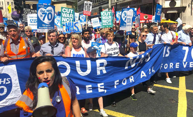Protester in scrubs leads the sunny Our NHS 70 march with megaphone
