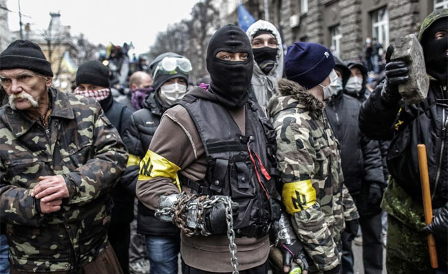 Masked and armed, the individuals who attacked the police nearly all had armbands with the neo-Nazi wolf's hook symbol, linking them to the far-right Social-National Assembly. Photo via Drugoi