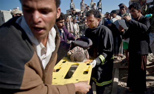 People carry the body of a child they uncovered from under the rubble of houses destroyed by Saudi airstrikes near Sanaa Airport, Yemen, Thursday, March 26, 2015. Photo: AP Photo/Hani Mohammed