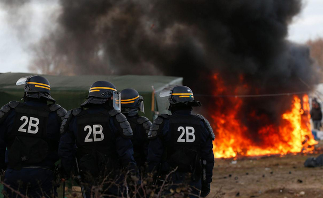 French police watch as huts burn