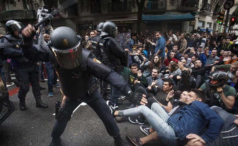 Police officers hitting protestors organised in passive resistance in Barcelona during the independence referendum of 2017. Photo: Wikipedia
