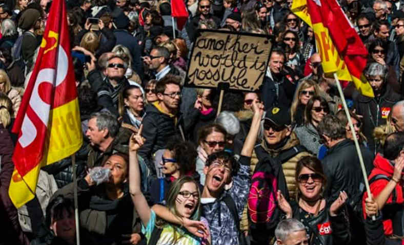 French students protest holding a placard that says 'another world is possible' in front of a crowd of people marching and red and yellow CGT union flags