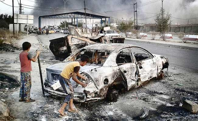 Children stand next to a burnt vehicle in the northern Iraq city of Mosul. Reuters