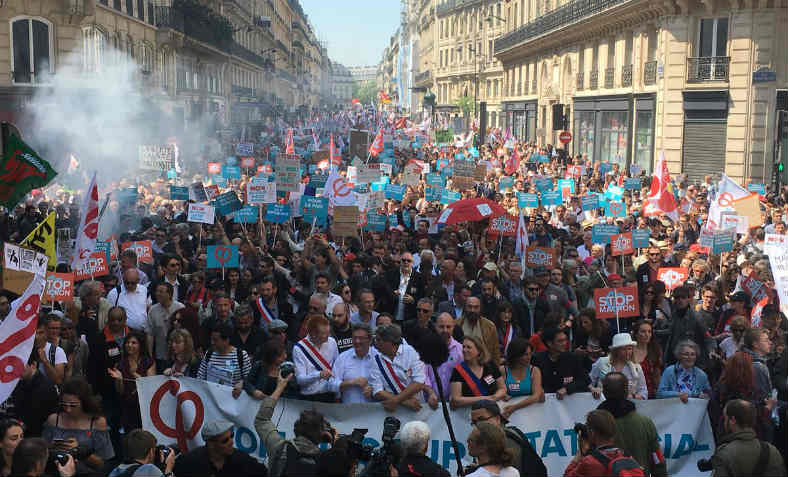 La France Insoumise leaders at the head of a massive marching crowd stretching back right into the distance of a Paris boulevard, with