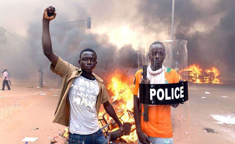 Protesters pose with a police shield outside the parliament in Ouagadougou on October 30, 2014. Photo: Issouf Sanogo/AFP/Getty Images