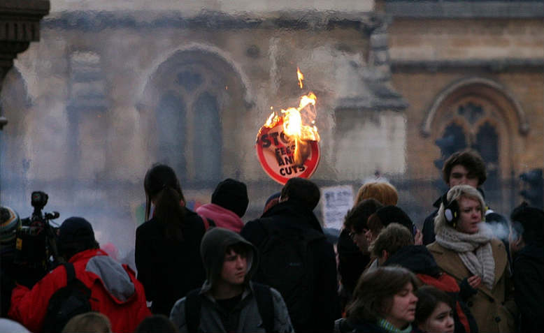 Burning 'stop fees and cuts' plarcard on student protests, Parliament Square, London, 2010. Flickr/ Bob Bob