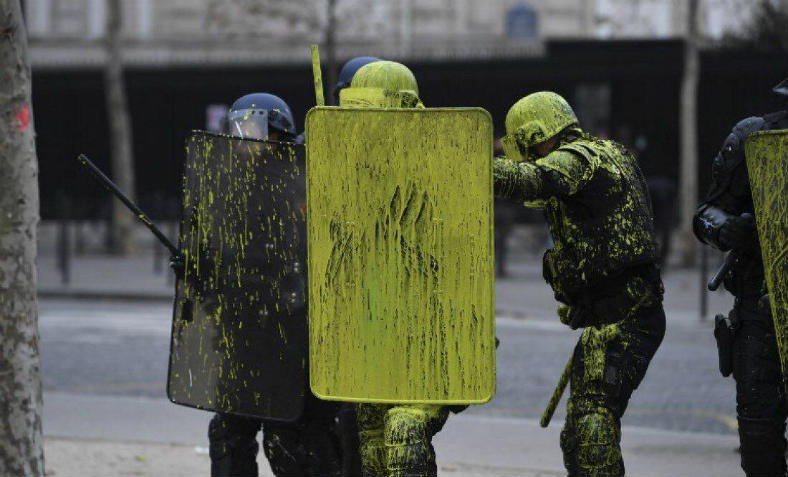 Riot police hit with yellow paint bombs in Paris on Saturday morning.  Photo: @giletsjaunesinfo