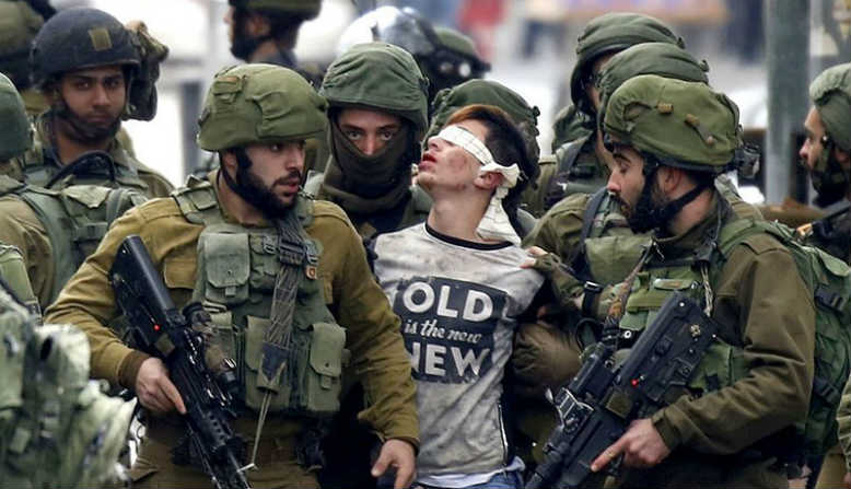 Israeli soldiers detaining a blindfolded Palestinian teenager. Photo: Wikimedia Commons