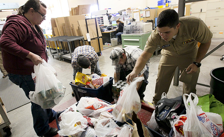 Volunteers weigh food drive donations. Photo: Wikipedia