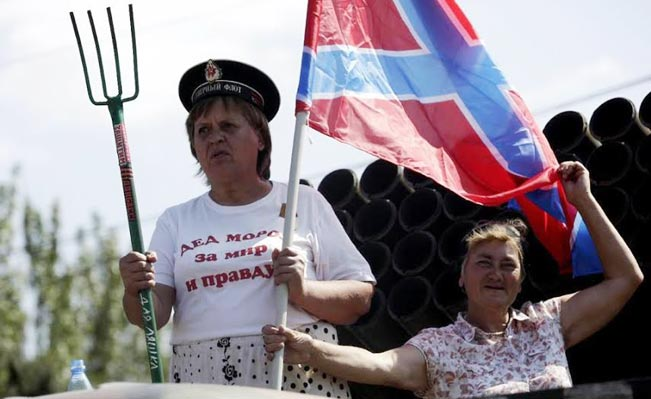 "A woman rides on the back of a truck holding a pitchfork and a flag of Novorossia (Newrussia, a union between the ""Donetsk People's Republic and ""Lugansk People's Republic) on August 24, 2014 in Donetsk, eastern Ukraine. Photograph: Max Vertov"