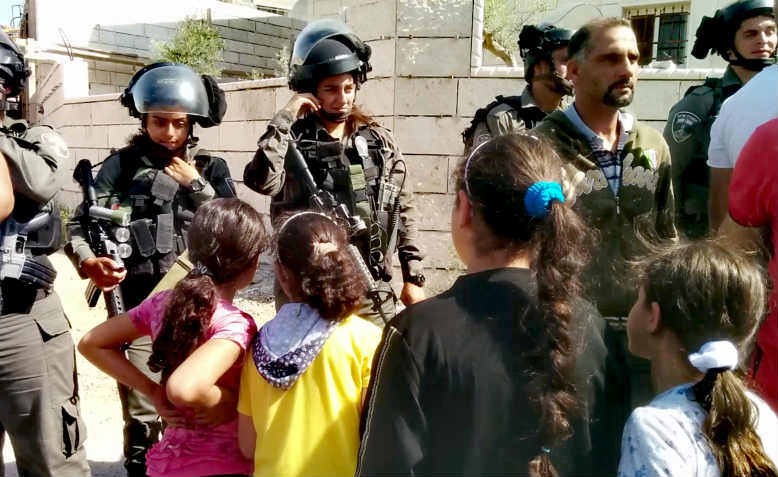 Palestinian children face Israeli soldiers at the house demolition protest in al-Walaja.