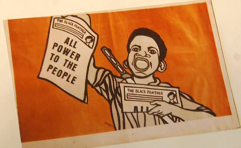 An iconic image from the Black Panther Party newspaper, with a young man waving copies of their newspaper, shouting (mouth open) and with an automatic rifle strapped to his back.