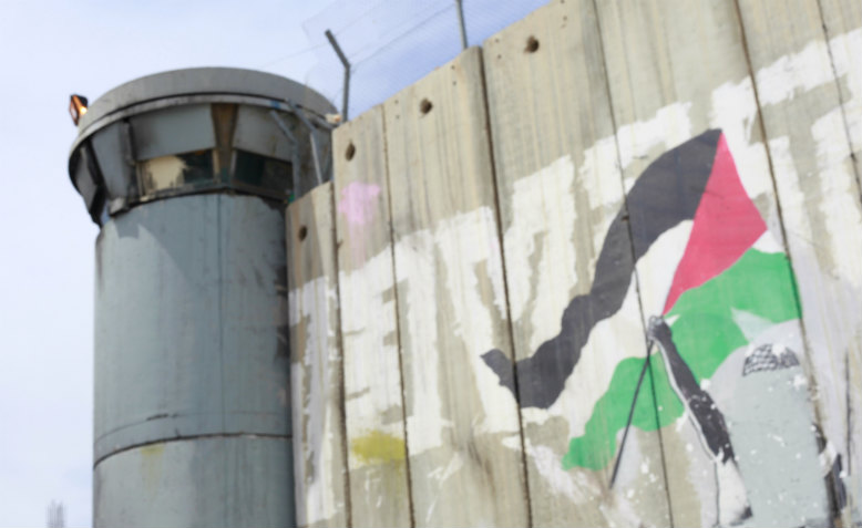 Israel's wall and a military turret in Bethlehem, West Bank, April 2013, on which has been neatly painted a Palestinian flag.