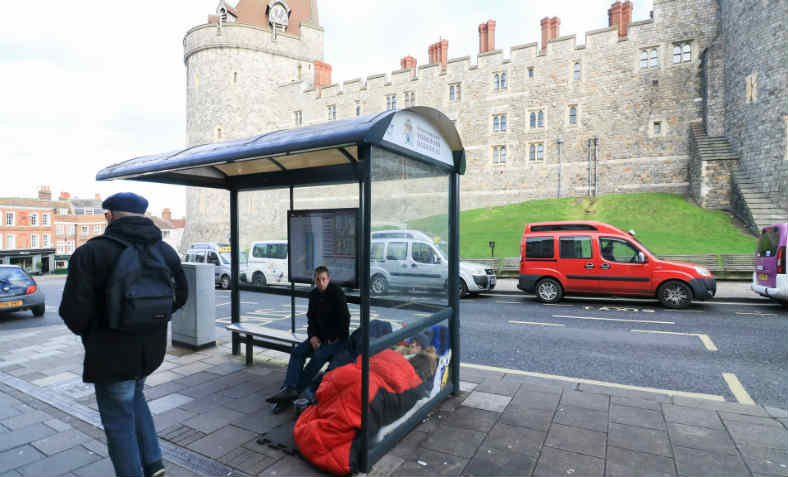 Homeless person in bus shelter next to Windsor Castle. Photo: Amer Ghazzal/Barcroft Images